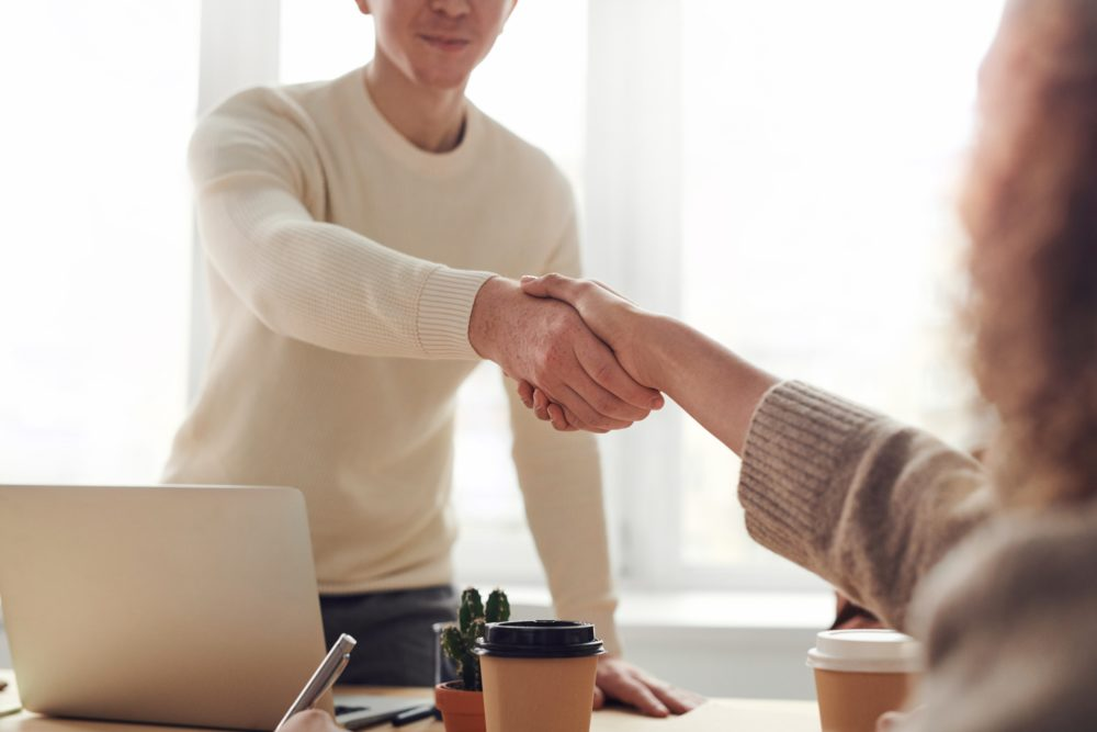 A contractor shaking hands with a contractor mortgage broker after a successful meeting