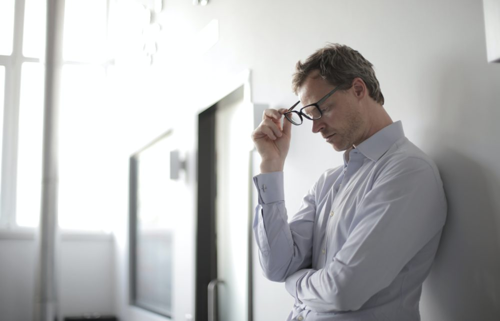 Contractor leaning against a wall looking frustrated